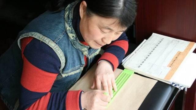 一位妈妈在为盲童抄写盲谱